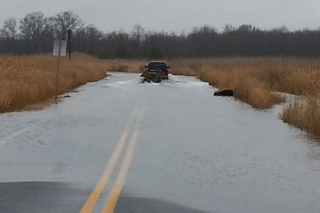 Pick-up truck driving through flooded road
