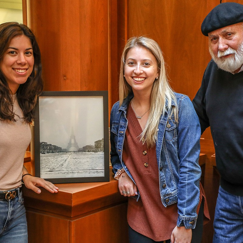 Two students and a faculty member stand next to a winning entry in the 2019 photo contest