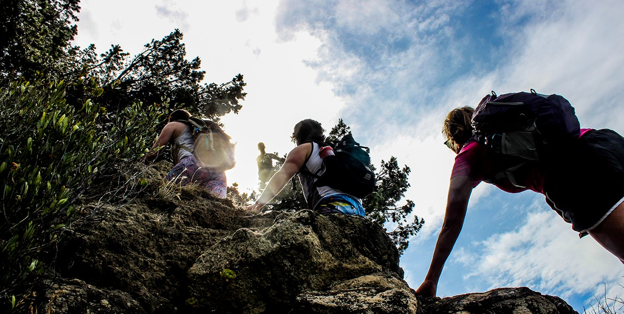 A group of UD students trek up a hill or mountain.