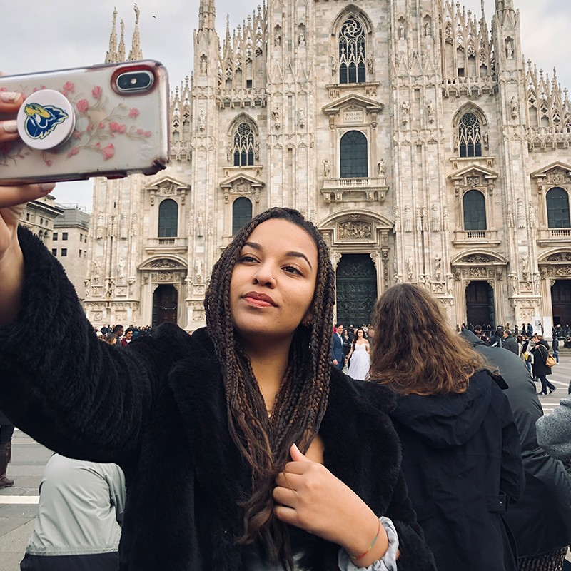 A photo of a student taking a selfie in front of an Italian landmark.