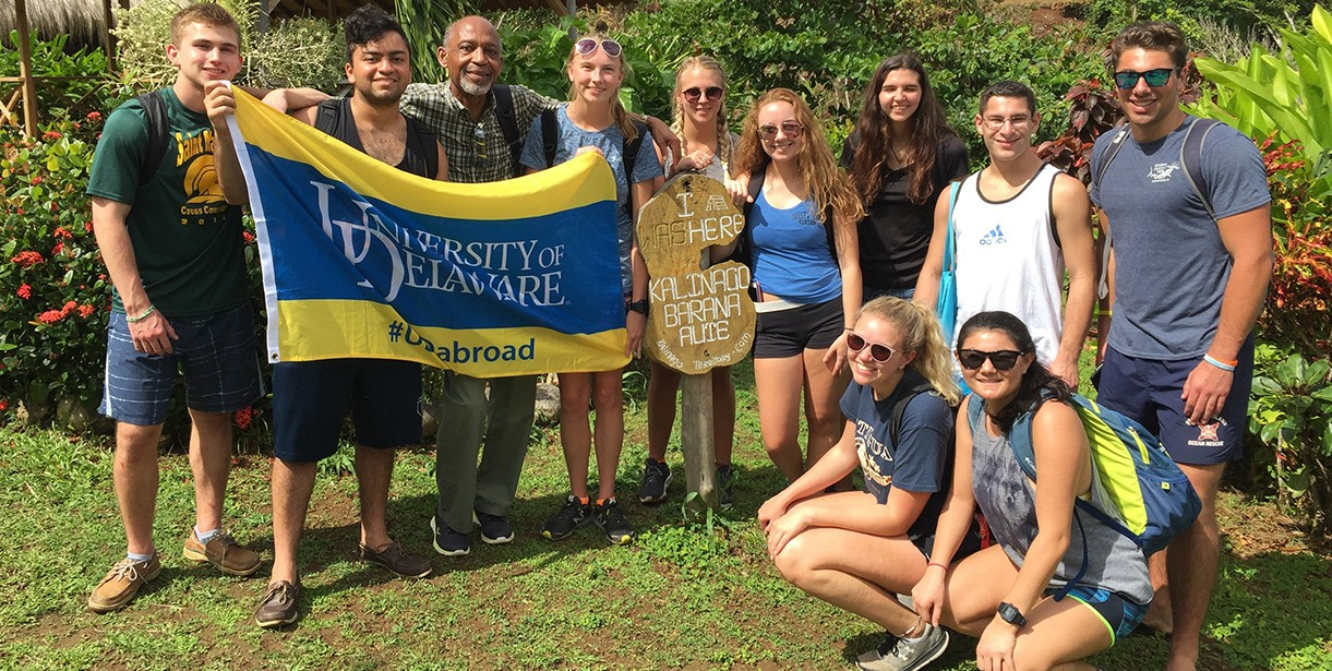 A group of students and their Study Abroad Faculty Director stand for a photo with the UD Flag in Dominica.