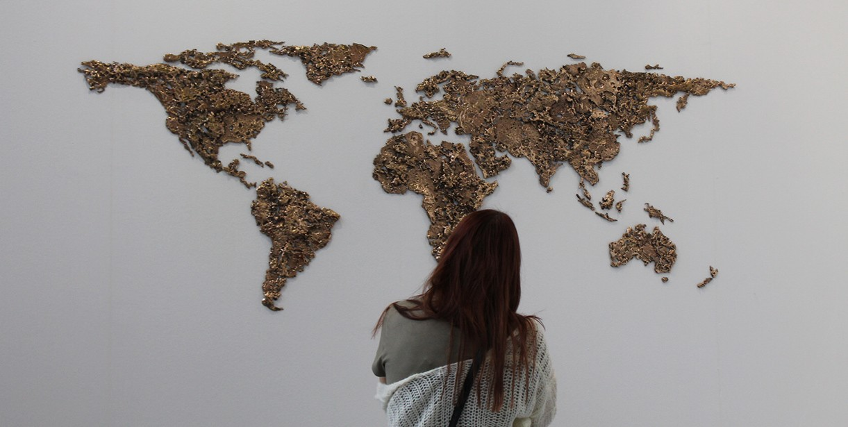 A student stands looking at a world map