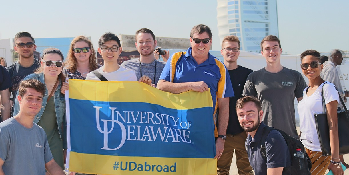 Study Abroad students and their faculty director stand with a #UDAbroad flag in Dubai