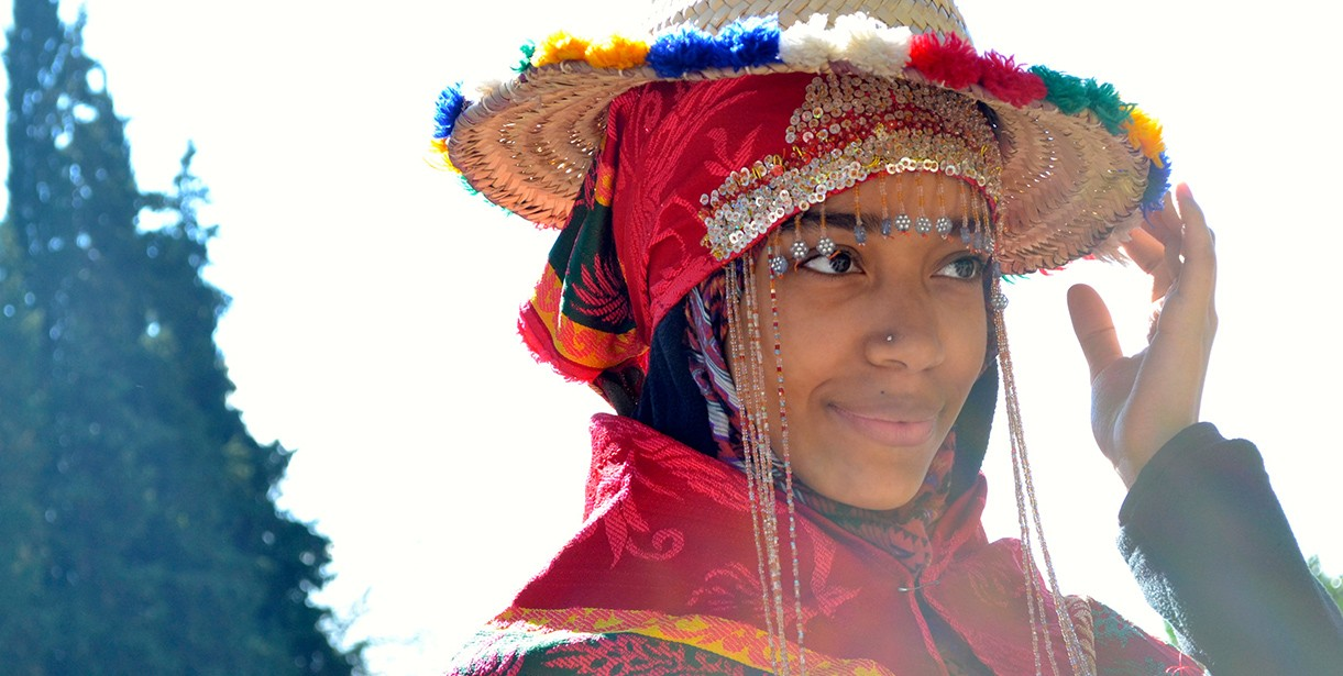 A photo of a student smiling and holding her hat in Morocco.