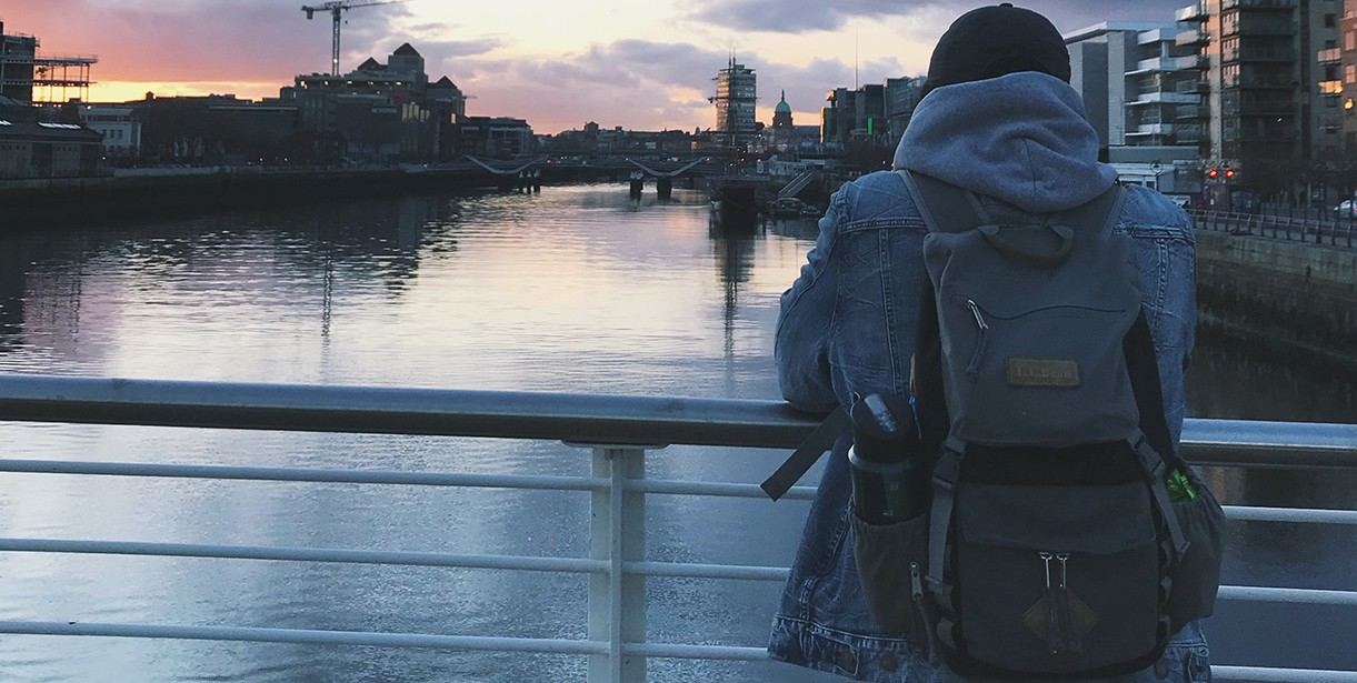 A Study Abroad student stands looking over an Irish cityscape and waterway.