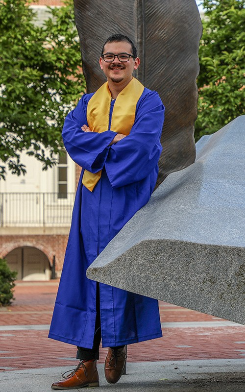 UD World Scholar Jed Hackett poses for a photo in his grad regalia by the UD Book Statue.