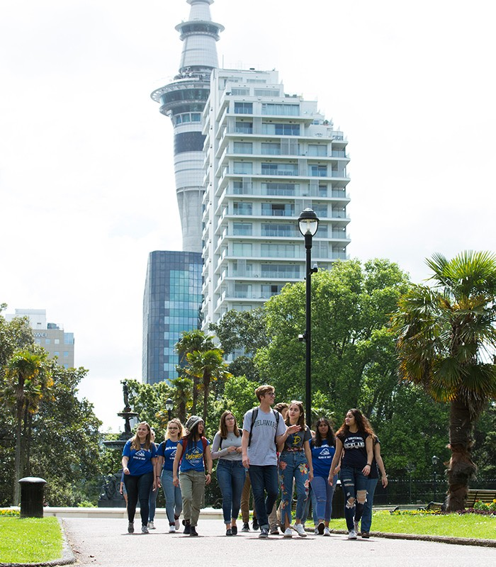 World Scholars walk through campus, surrounded by buildings and greenery.