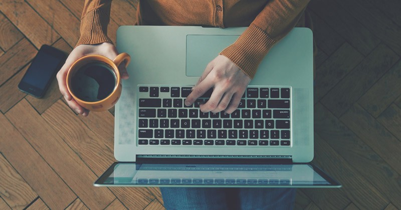 A person works on a laptop with a cup of coffee in their hand.