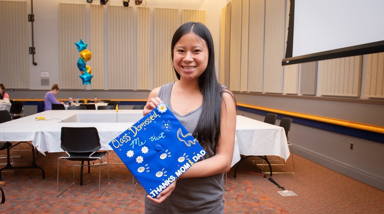 A student shows off her decorated graduation cap at an event sponsored by DAR.