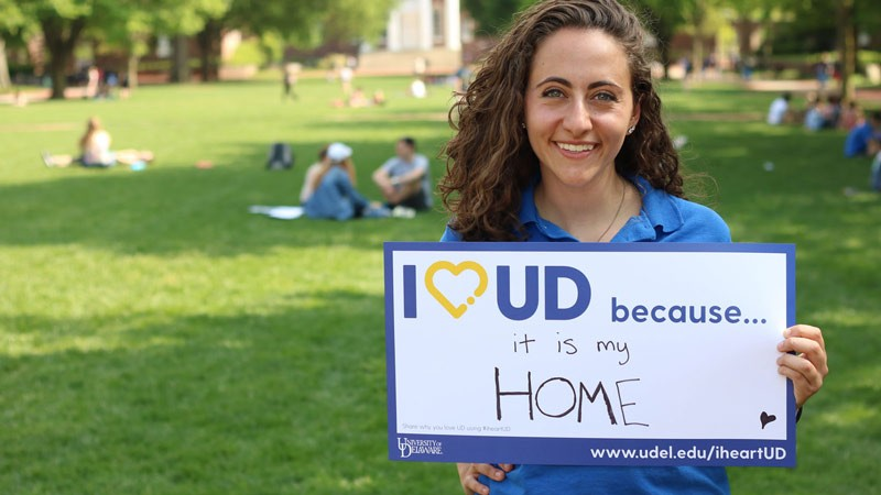 A student displays a sign stating why she hearts UD on I heart UD day.