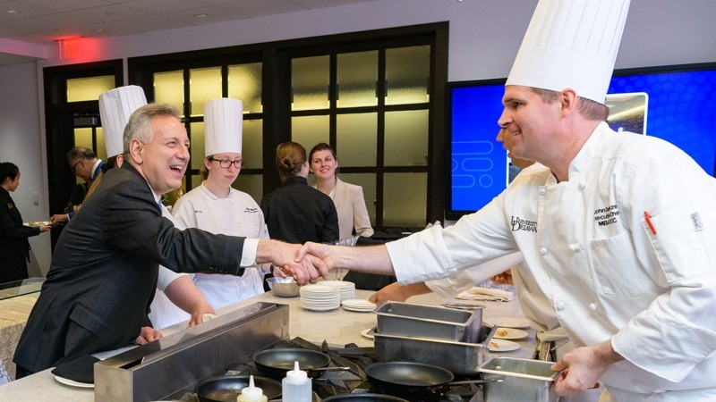 UD President Dennis Assanis (left) shakes hands with Executive Chef John Deflieze during the celebration of the Vita Nova renovation.