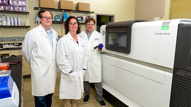 UD researchers stand in front of lab equipment in white lab coats.