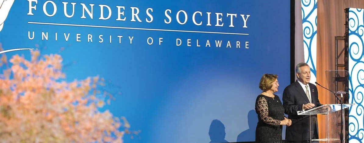President Dennis Assanis and First Lady Eleni Assanis stand at the podium during a Founder's Society event.