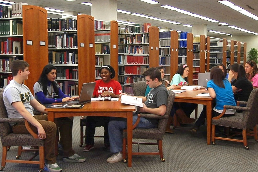 Students sit at tables in groups in Morris Library on the University of Delaware campus.