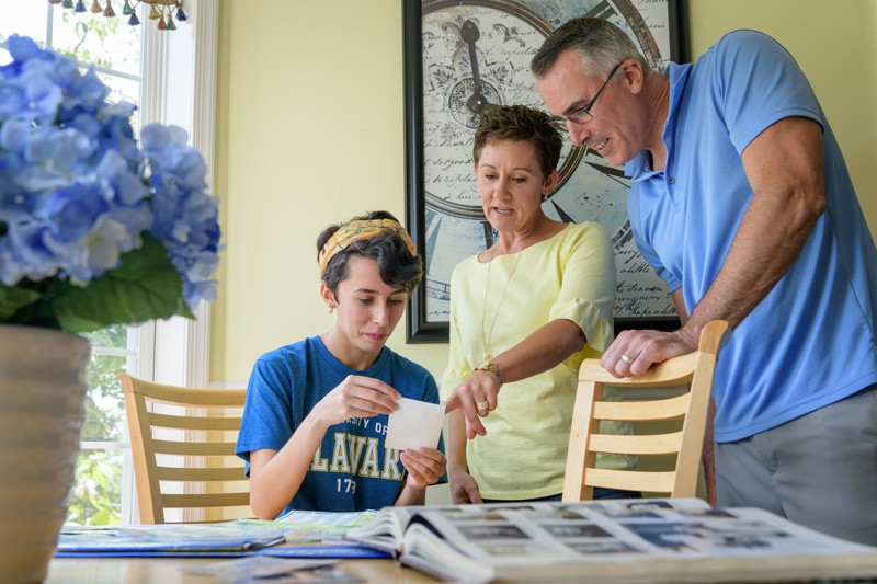 A UD student sits at a table while her parents stand over her looking at photographs together.