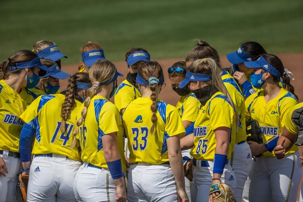 Two UD women's field hockey players hold a trophy above their heads while onlookers celebrate in the background.