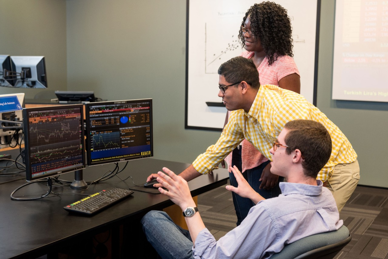A female and two male UD students work together at a computer.
