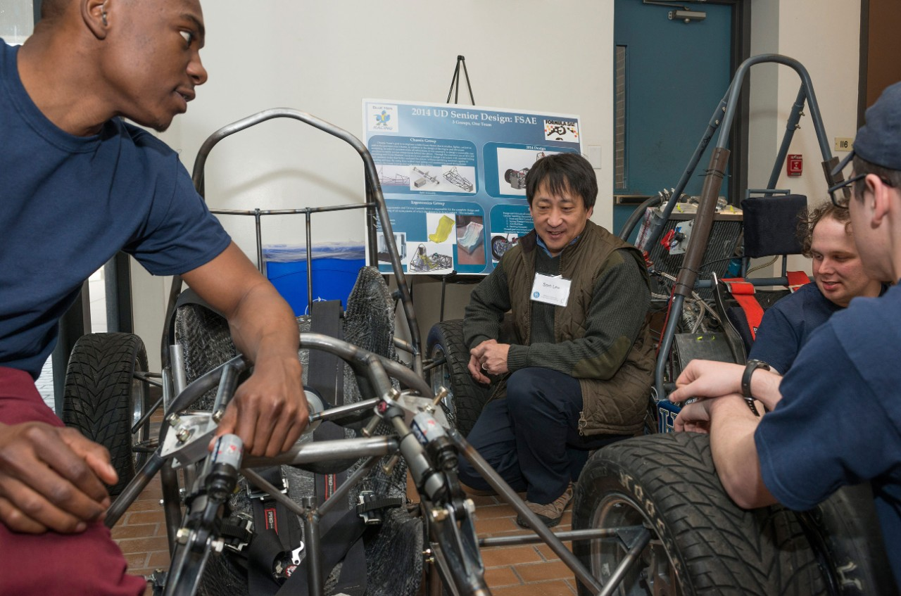 Four UD researchers work together on a one-man vehicle.