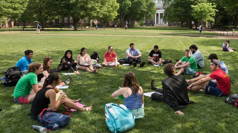 a circle of UD students sitting outside on the green