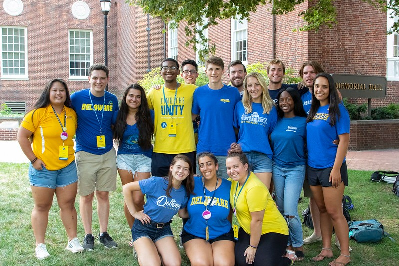 A diverse group of young students wearing blue & gold shirts