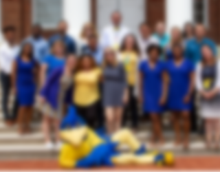 Smiling photo of our staff with the UD mascot, YoUDee.