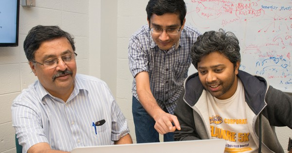 Left to right, pProfessor Vijay Shanker reviews data with graduate students Samir Gupta and Ashique Mahmood.