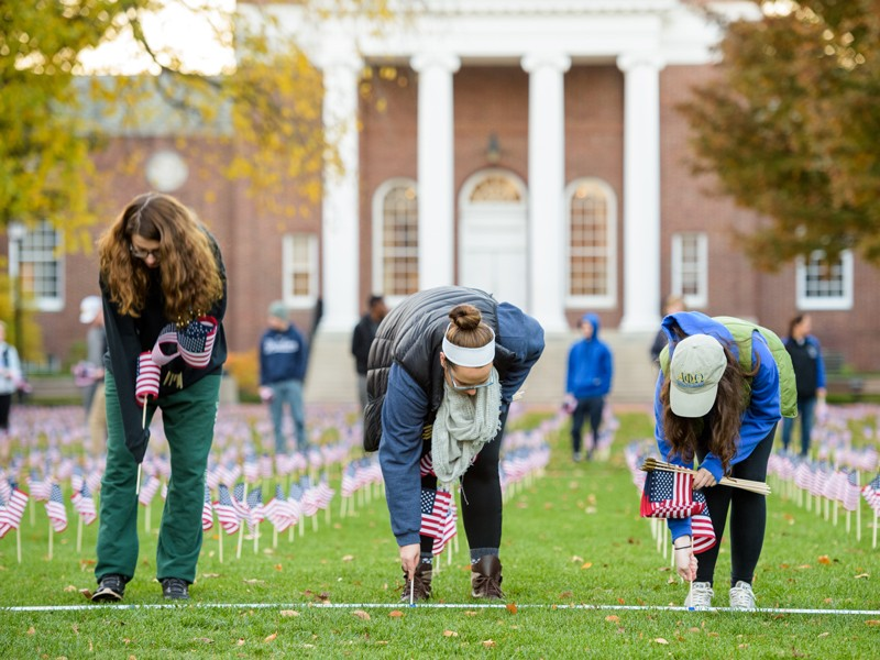 Students help plant flags on The Green to observe Veterans Week activities in 2016