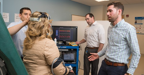 Researcher Christopher Martens (right) is investigating nicotinamide riboside's impact on age-related diseases like mild cognitive disorder and dementia. In this photo, lab coordinator Joshua Hobson (center) runs the computer while graduate student Theodore DeConne (left) uses an ultrasound probe to measure brain blood flow.