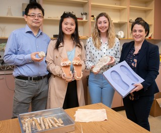 The project team consists of (from left) Huantian Cao, holding a mushroom mycelium sample; Wing Tang, with the prototype shoe whose top she designed and made; Jillian Silverman, with mycelium she grew in the shape of a sole; and Kelly Cobb, holding the mold in which the sole-shaped mycelium was grown.