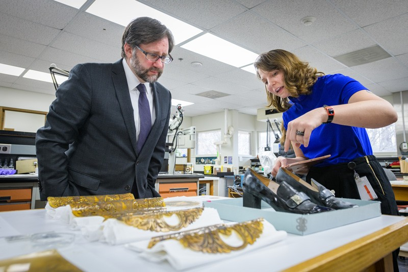 In the objects conservation lab, Winterthur/UD Program in Art Conservation (WUDPAC) student Natalya Swanson shows Jon Parrish Peede a pair of shoes from the 1968 Dior collection, sent to Winterthur by the Philadelphia Museum of Art for cleaning.