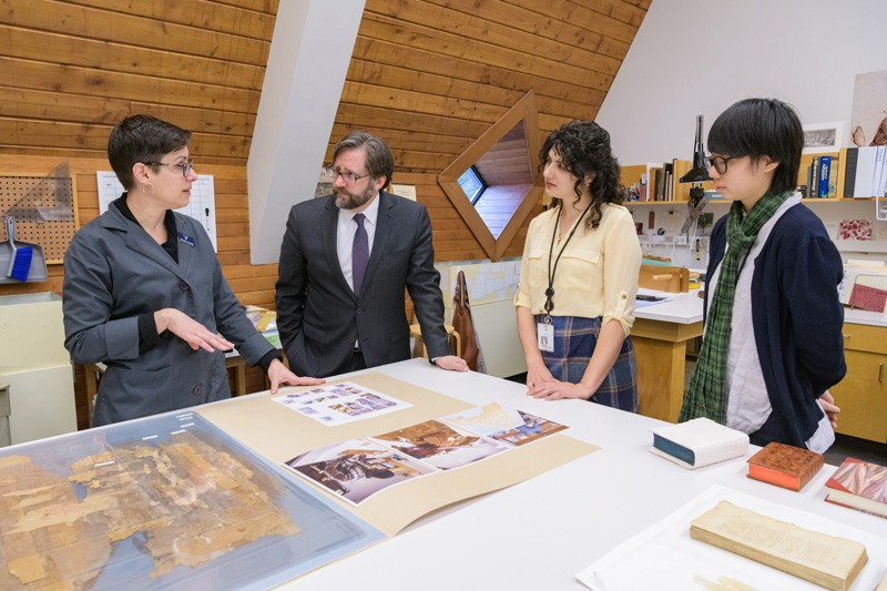 Melissa Tedone, Winterthur book and library conservator and affiliated WUDPAC faculty member, discusses the program's focus on training future library and archives conservators with NEH Chairman Jon Parrish Peede as WUDPAC students Yan Choi (far right) and Karissa Muratore listen.