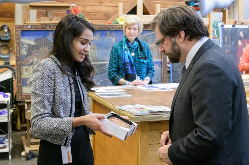 WUDPAC student Julianna Ly shows NEH Chairman Jon Parrish Peede fragments of a flag that were part of a damaged diorama, now undergoing conservation treatment, depicting Arctic exploration. Debra Hess Norris (center), the Unidel Henry Francis du Pont chair in Fine Arts and chair of the Department of Art Conservation looks on.