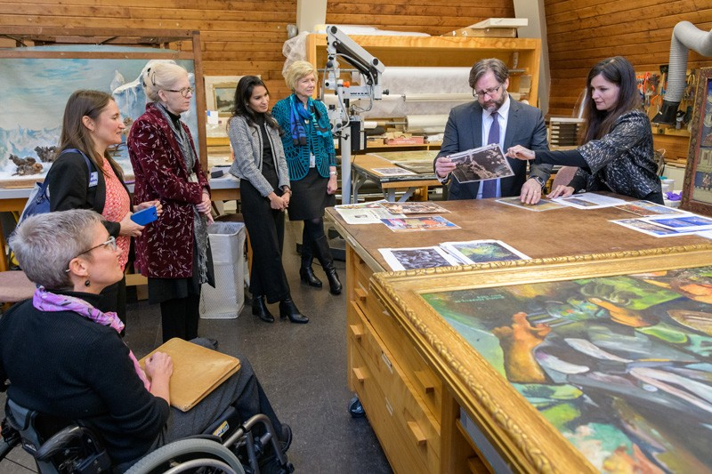 Winterthur/UD Program in Art Conservation student Jennifer Myers (far right) shows Jon Parrish Peede photos of work that has been done in the paintings conservation lab.