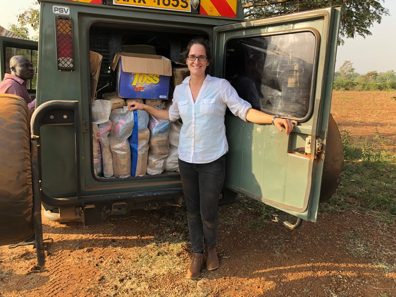 Leah Palm-Forster stands with their research vehicle stocked with the packets of corn seed used in their economic experiments. Nearly 1,000 pounds of seed were purchased for the project.