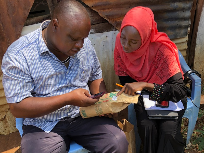 University of Delaware alumnus Mariam Gharib (right) helps a Kenyan farmer verify the corn seed's authenticity by submitting the certification code listed on the seed packet to the manufacturer via a text from his cell phone.