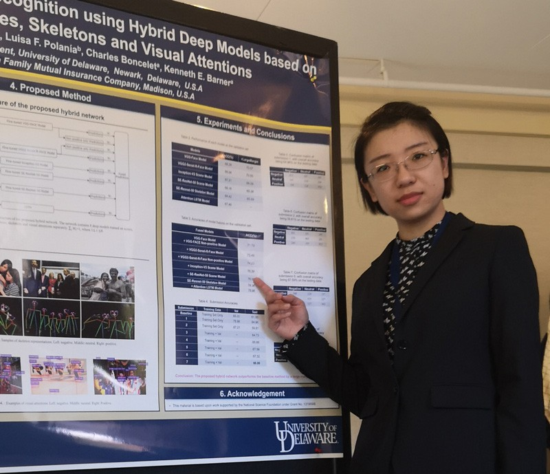 Xin (Cindy) Guo points to a poster used in presenting her group's research