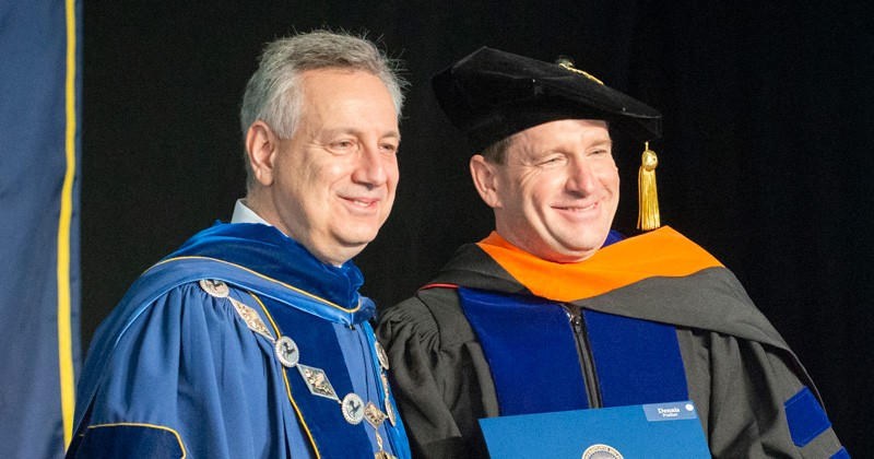University of Delaware President Dennis Assanis (left) presents Engineering Professor Dennis Prather with the 2018 Outstanding Doctoral Graduate Advising and Mentoring Award during UD's doctoral hooding ceremony on Friday, May 25.