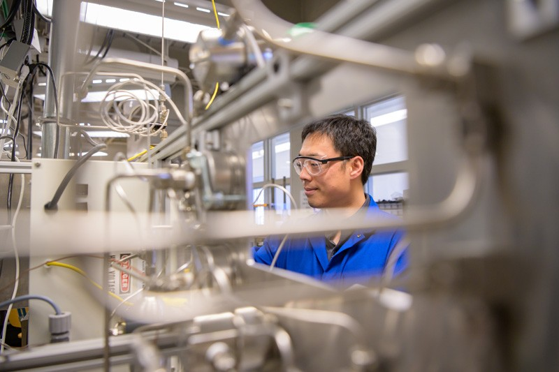Bingjun Xu, an assistant professor of chemical engineering, is pictured with a tool his research group developed to determine the oxidation state of catalysts.