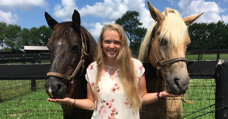 UD pre-veterinary medicine and animal biosciences major Jenna Deal stands with horses at Camden Training Center in South Carolina.