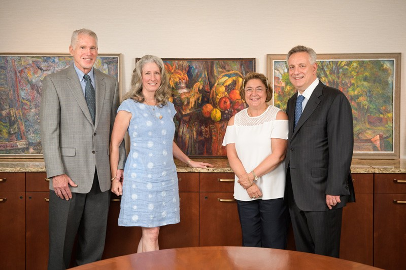 University of Delaware alumnus David Baldt, Sandra Baldt, Eleni Assanis and UD President Dennis Assanis stand in front of newly donated Edward Loper paintings that will now be part of the University's collections.