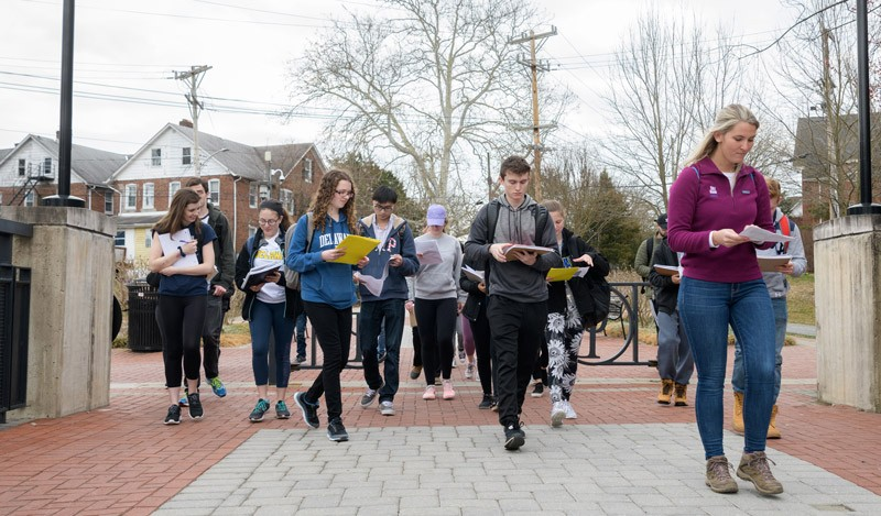 June Hazewski, UD master's student and teaching assistant for the geology lab, leads a group of across the bridge on the Laird Campus.