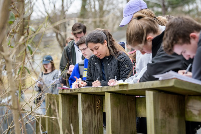 Students take notes on the water level of White Clay Creek.