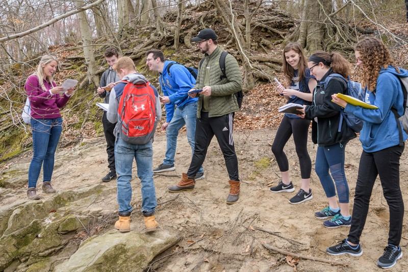 Standing over the dam on White Clay Creek, teaching assistant June Hazewski talks to geology students about the impact flooding would have on the dam.