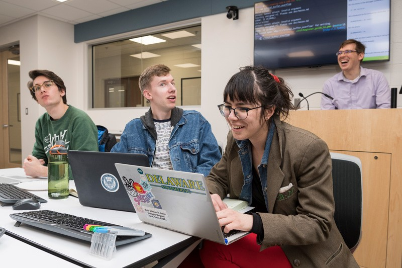 From left to right, students Ryan Geary, Collin Clark, and Isabel Navarro work on projects in the UD's iSuite in Evans Hall, while assistant professor of electrical and computer engineering Andy Novocin shares advice.