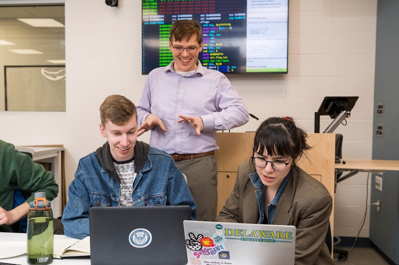 Students Collin Clark (left) and Isabel Navarro (right) learn from Andy Novocin (standing), an assistant professor of electrical and computer engineering.