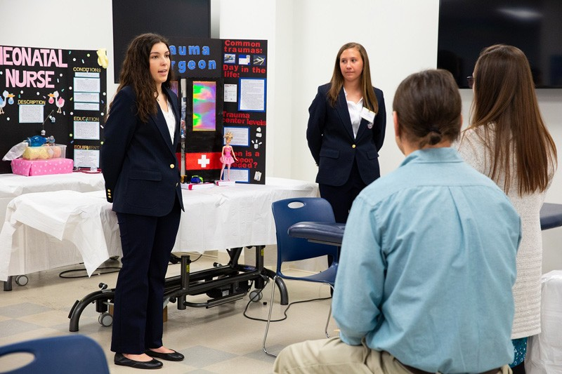 Middletown High School students Madison DeCook (far left) and Taylor Waltemire explain the extensive skills and training needed to become a trauma surgeon. The students earned a silver medal in the health career display competition during the HOSA conference.