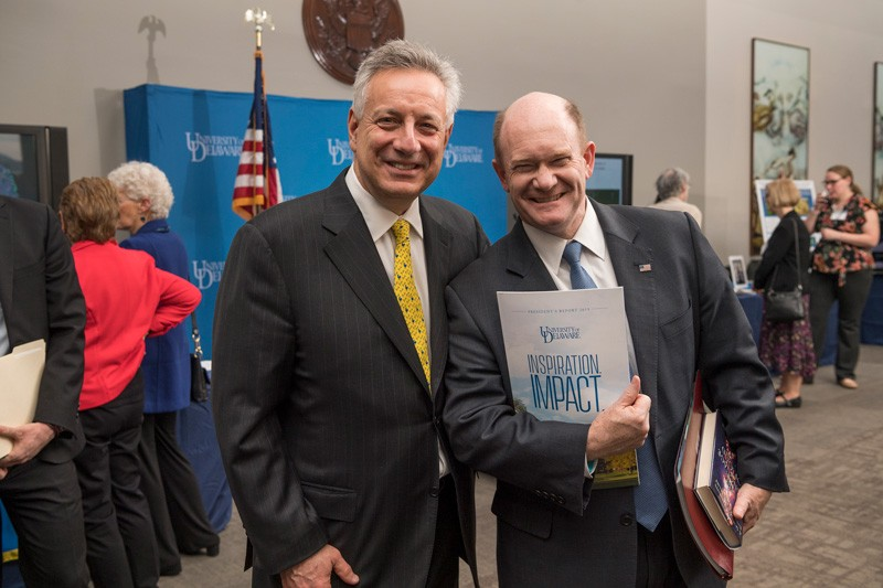 U.S. Senator Chris Coons (right) has a degree in chemistry and is a powerful advocate for University of Delaware research. Here he shows off his new copy of UD President Dennis Assanis' annual report.