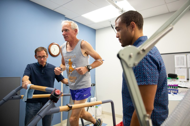 Kinesiology and Applied Physiology Professor Bill Farquhar (left) and postdoctoral research associate Austin Robinson (right) watch 71-year-old marathoner Gene Dykes on the treadmill as part of their research.