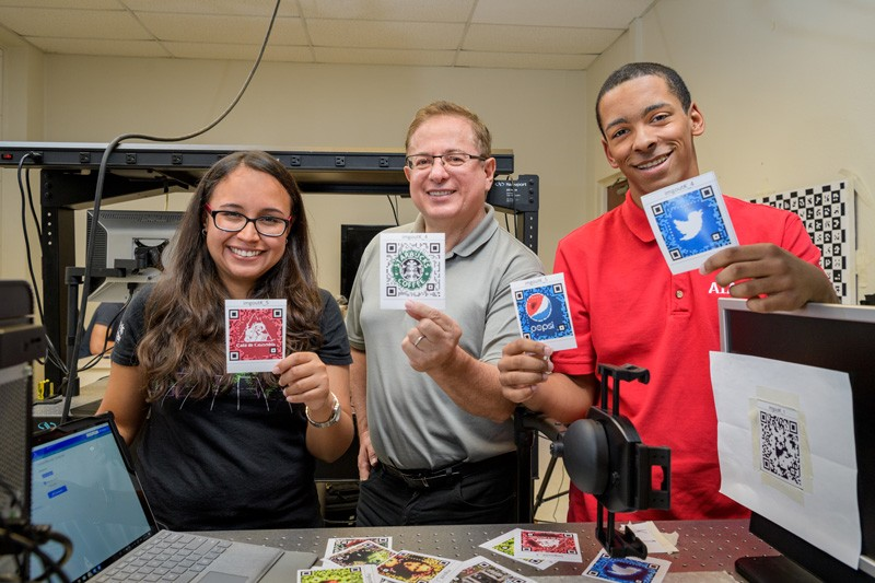 From left to right, UD doctoral student Karelia Pena; Gonzalo Arce, Charles Black Evans Professor of Electrical and Computer Engineering; and David Miller, a student at Mount Pleasant High School in Wilmington, Delaware, show the QR codes they have studied using sophisticated optical.