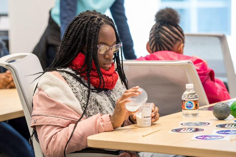 A girl makes oobleck, a slime that exhibits properties of both solids and liquids, during a session about rheology, the study of how liquids and solids flow.